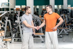 Hello athletes. Hello two athletes at the fitness club. Two beau Royalty Free Stock Photography