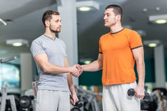 Hello athletes. Two athletes shake hands at the fitness club. Tw Stock Image