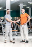 Hello athletes. Two athletes shake hands at the fitness club. Tw Royalty Free Stock Image