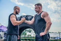Hello athletes. Two athletes shake hands at the street gym. Two beautiful men stand among the big tire. Two Strong man confident royalty free stock photo