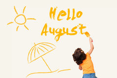 Hello August. Cute little girl writing Hello August - using painting brush on wall background Stock Photo