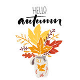 Hello autumn calligraphy with illustration of bunch of maple and golden leaves. Inspirational saying fall design. Stock Photo