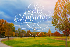 Hello Autumn calligraphy lettering text on Beautiful autumn alley in the park with colorful trees Royalty Free Stock Photo