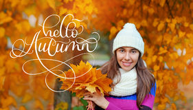 Hello Autumn calligraphy lettering text on Beautiful autumn woman in golden park Stock Photos