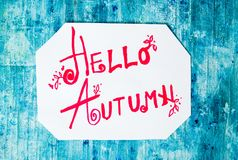 Hello Autumn calligraphy note with fallen leaves. On blue board stock photography