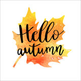 Hello autumn. Hand lettering phrase on orange watercolor maple leaf background Royalty Free Stock Photography