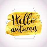 Hello Autumn. Vector illustration of lettering phrase on golden paint stain banner. Vector gold paint. Autumn calligraphy composition with gold brush painted Royalty Free Stock Image