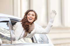 Hello! Beautiful Young Woman Looking Out From A Car Saying Hello Royalty Free Stock Photos