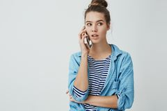 Hello can I order. Portrait of cute casual good-looking fashionable woman messy hairbun looking aside thoughtful holding stock image
