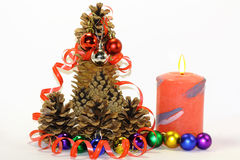 Hello Christmas tree, New year. The design of fir cones reminiscent of the new years tree, the festive atmosphere of the candle, the colored balls, serpentine Royalty Free Stock Images