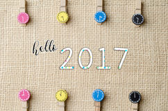 Hello 2017 with colourful wooden clothespins on burlap sack background. Stock Image