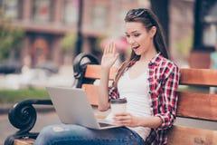 Hello där! Unga flickan vinkar till skärmen till hennes pojkvän arkivbild