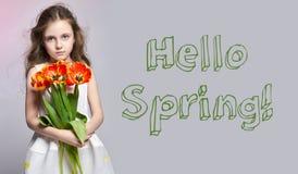 Hello-de Lente, 8 maart Manier roodharig meisje met tulpen in handen Studiofoto op licht gekleurde achtergrond De dag van de lent Royalty-vrije Stock Foto's
