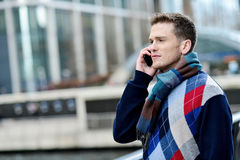 Hello dear, i am waiting for you here. Sideways of male listening on mobile at outdoor royalty free stock photography