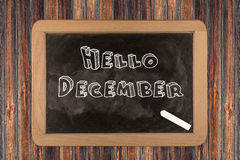 Hello December  - chalkboard. Hello December - chalkboard with 3D outlined text - on wood Royalty Free Stock Images