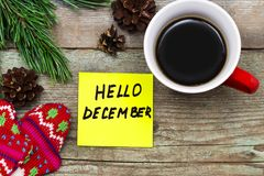 Hello December- handwriting in black ink on a sticky note with. A cup of coffee and mittens, New Year resolutions concept royalty free stock photos