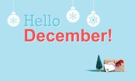 Hello December meddelande med det julgåvaasken och trädet royaltyfri fotografi