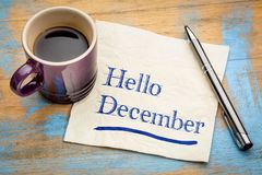 Hello December note on a napkin. Hello December  - handwriting on a napkin with a cup of espresso coffee Stock Image