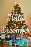 "Hello December. Text ""Hello December"" superposed on colorfully decorated Christmas tree  surrounded at the base by parcels containing presents, cream background Royalty Free Stock Photos"
