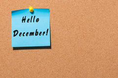 Hello December written on blue paper pinned at cork notice board with empty space for text. Eve, Christmas and New year Royalty Free Stock Images