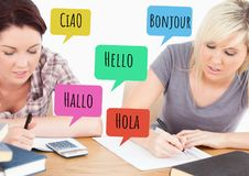 Hello in different languages chat bubbles learning with students. Digital composite of Hello in different languages chat bubbles learning with students Royalty Free Stock Photo