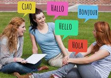 Hello in different languages chat bubbles learning with students. Digital composite of Hello in different languages chat bubbles learning with students Royalty Free Stock Photos