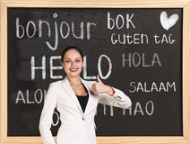 Hello in different languages. Woman near words hello in different languages on chalkboard royalty free stock photos