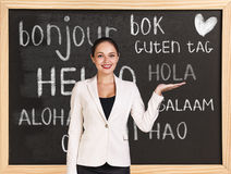 Hello in different languages. Woman near words hello in different languages on chalkboard stock photos