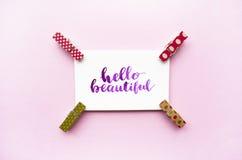 Hello för inspirerande citationstecken härligt handskrivet med vattenfärgen i kalligrafistil, miniatyrklädnypor på en rosa bakgru Arkivfoto