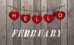 Hello februari bij het hangen van rode harten en oude houten achtergrond wordt geschreven die royalty-vrije stock foto