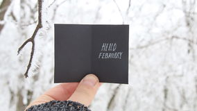 Hello February concept, inscription on a beautiful winter background. Hello February creative concept, man holding a card with text stock footage