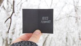 Hello February creative concept. Man holding a card with text stock video