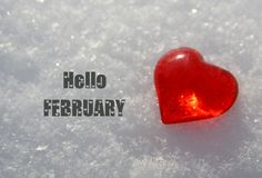 Hello February.Decorative red heart on natural white snow background.Winter holidays or Valentines Day concept. royalty free stock image