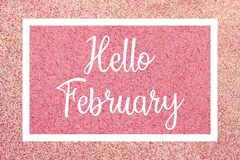 Hello February greeting card with white text over a pink glitter background. Hello February greeting card message, White text and frame against a shiny pink vector illustration
