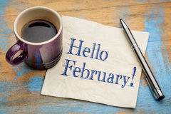 Hello February on napkin. Hello February - handwriting on a napkin with a cup of coffee stock image