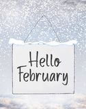 Hello February text on white plate board banner with cold snow f royalty free stock images