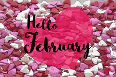 Hello February. Text 'Hello February' in black script written over a pink heart shape all superposed on a surface composed of red, pink and white heart shaped Royalty Free Stock Images