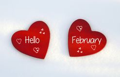 Hello February.Two red wooden hearts on natural white snow background.Winter holidays or Valentines Day concept. royalty free stock photo