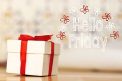 Hello friday message with white gift box with red ribbon on wood background. Hello friday message with white gift box with red ribbon stock photo