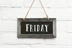 Hello friday text on hanging board white brick outdoor wall. Hello friday finally weekend text on hanging board white brick outdoor wall royalty free stock photos