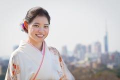 Hello from Fukuoka, Japan. A beautiful young woman in graduation kimono with the city of Fukuoka, Japan, in the background royalty free stock photo