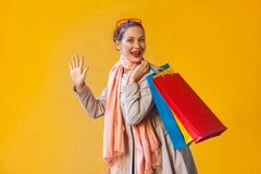 Hello! Happiness young adult woman with freckles, collect hair,. Looking at camera, hand up , holding many shopping bag, enjoying good shopping day. Studio shot stock photo