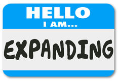 Hello I Am Expanding Name Tag Sticker Growth Expansion Increase. Hello I am Expanding words on a name tag sticker to illustrate growth, expansion or increase in Royalty Free Stock Photo