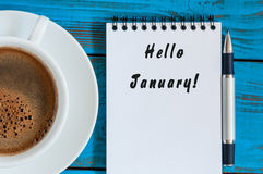 Hello Januari som är skriftlig på pappers- near arbetsplats för morgonkaffekopp Begrepp för tid för nytt år Affär och kontorsbakg Fotografering för Bildbyråer