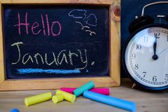 Hello january. Back to school concept. Alarm clock on wooden with blackboard on background royalty free stock image