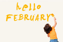 Hello JANUARY. Cute little girl drawing : hello FEBRUARY with painting brush on wall background Stock Photography