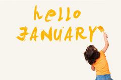 Hello JANUARY. Cute little girl drawing : hello JANUARY with painting brush on wall background Royalty Free Stock Photos