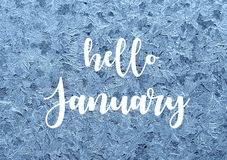 Hello January.Frosty natural pattern on winter window.Ice embroidered lace on the glass with text. Selective focus royalty free stock photography