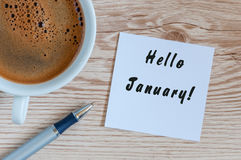Hello January greeting on paper at home or office workplace, near morning cup of coffee. business background.  Royalty Free Stock Photography