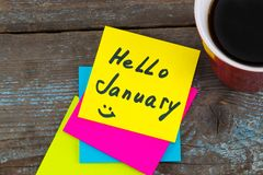 Hello January - handwriting in black ink on a sticky note with a. Cup of coffee, New Year resolutions concept Stock Photos